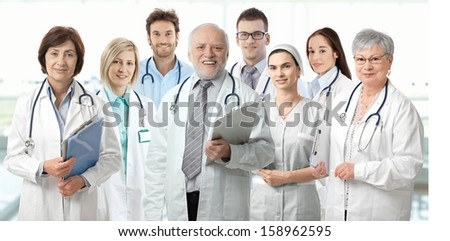 Team portrait of medical doctors looking at camera, smiling.