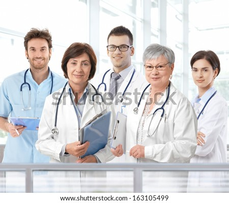 Team portrait of mixed aged medical doctors standing in hospital lobby, looking at camera, smiling. - stock photo