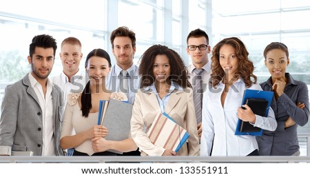 Team portrait of young and successful business people looking at camera, smiling. - stock photo