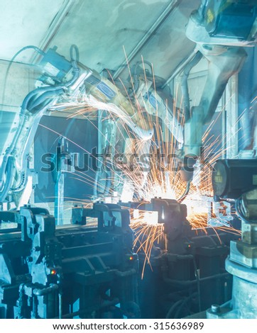 Team Robot welding  movement Industrial automotive part in factory  - stock photo