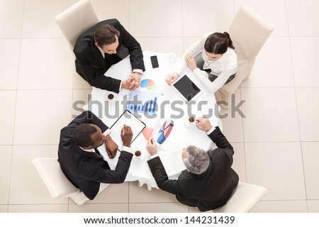 Team sitting behind desk, checking reports, talking. Top View - stock photo