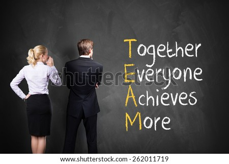 team stands in front of a blackboard with the crossword TEAM - together everyone achieves more - stock photo
