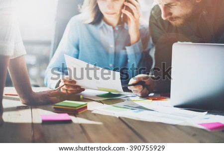 Team succes. Photo young business managers  working with new startup project in modern loft. Generic design notebook on wood table, talking smartphone, papers, documents. Horizontal, sunlight effect - stock photo