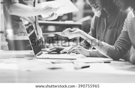 Team succes. Photo young talent managers crew working with new startup project in modern loft. Generic design notebook on wood table. Horizontal, film effect, black and white - stock photo