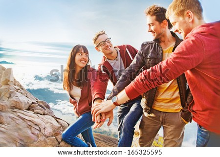 team success concept: group of people holding hands on the top of the mountain - stock photo