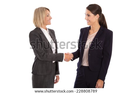 Team: Two isolated businesswoman shaking hands wearing business outfit  - stock photo