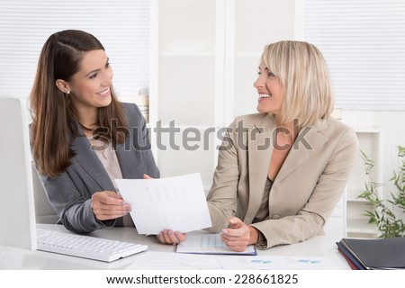 Team: two successful businesswoman sitting at desk having fun at work.