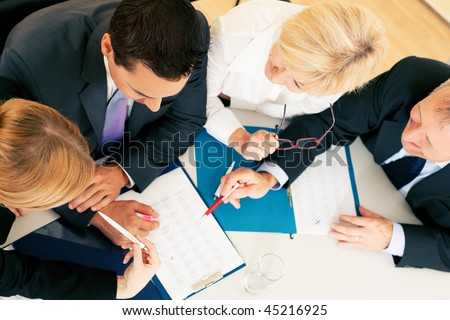 Team - two young workers and two senior people -  working hard, discussing contractual documents or spreadsheets - stock photo