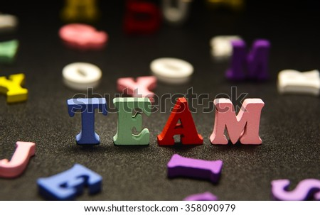 TEAM - word made from multicolored child toy  letters on black background - stock photo