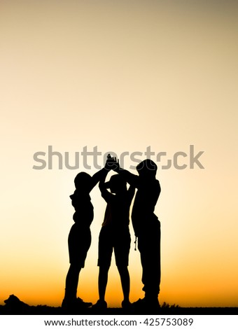 Team work and cooperation,  silhouette children with sunrise background.