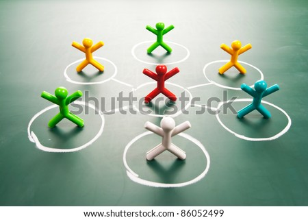 Team work concept. Colorful dolls on blackboard. - stock photo