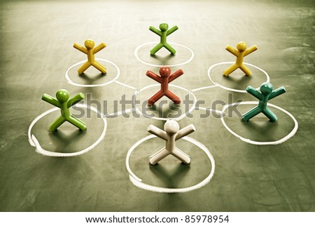 Team work concept. Colorful dolls with grungy blackboard. - stock photo