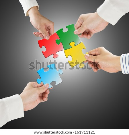 Team work concept, Hands hold puzzles connect each other with gray background - stock photo