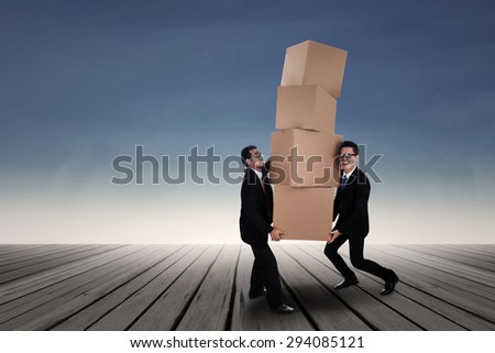 Team work concept; Two Asian business men carrying heavy boxes - stock photo