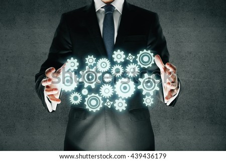 Team work concept with businessman in suit holding abstract gears on dark concrete background - stock photo