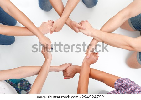 Team work. Group of young friendly people making ring of hands on white isolated background. - stock photo