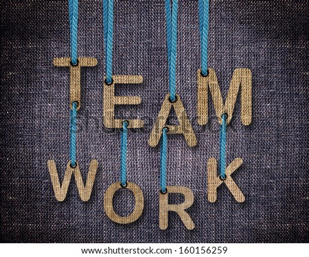 Team work Letters hanging strings with blue sackcloth background. - stock photo