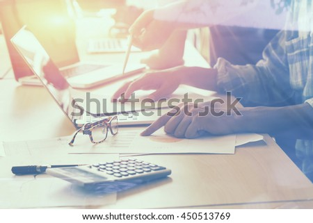 Team work meeting concept,business documents on office table with laptop computer and graph financial with social network diagram and colleagues discussing data.selective focus,vintage color - stock photo