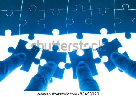 Team work on solving puzzle problem. Team work concept. - stock photo
