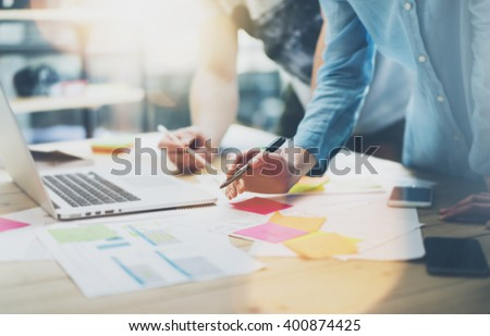 Team work process.Photo young business managers crew working with new startup project.Notebook on wood table, typing keyboard.Using modern smartphones, texting message, analyze plans. Film effect - stock photo