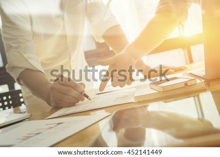 Team work success.business managers working with new startup project in modern office.Businessman adviser analyzing financial figures denoting the progress in the work of the company,vintage color - stock photo