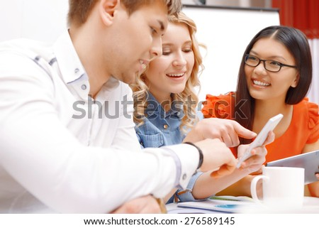 Team work. Team of young app developers looking at smartphone and pointing at it joyfully close up - stock photo