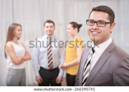 Team work. Young confident businessman in formalwear and glasses looking with a smile straight at a camera with his team discussing something on the background in blurry - stock photo