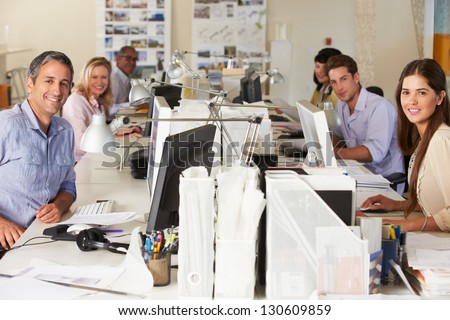 Team Working At Desks In Busy Office - stock photo