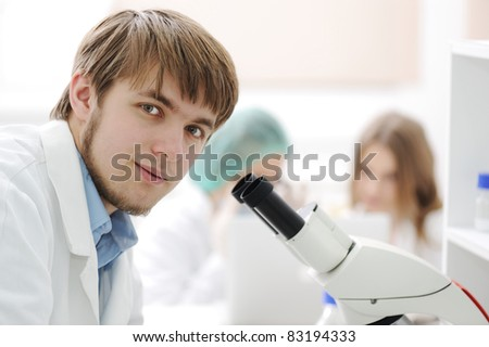 Team working with microscopes in a laboratory - stock photo