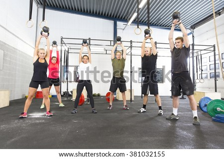 Team workout with kettlebells at fitness gym - stock photo