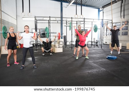 Team workout with weights at fitness gym center - stock photo