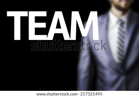 Team written on a board with a business man on background - stock photo