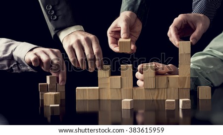 Teamwork and cooperation concept - five male hands building a structure of wooden blocks on black desk with reflection, toned retro effect. - stock photo