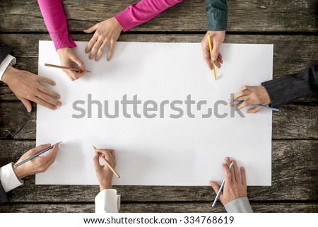Teamwork and cooperation concept - top view of six people - men and women - drawing or writing on a large white blank sheet of paper. - stock photo