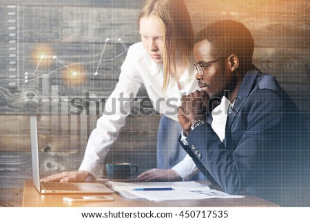 Teamwork and cooperation. Redhead Caucasian female worker in white shirt showing a presentation on generic laptop to her African American boss in formal suit, sitting at the desk. Double exposure - stock photo