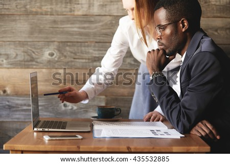 Teamwork and cooperation. Redhead Caucasian secretary in white shirt, holding a pen, pointing at the screen of generic laptop, showing a presentation to her African American boss in formal suit - stock photo