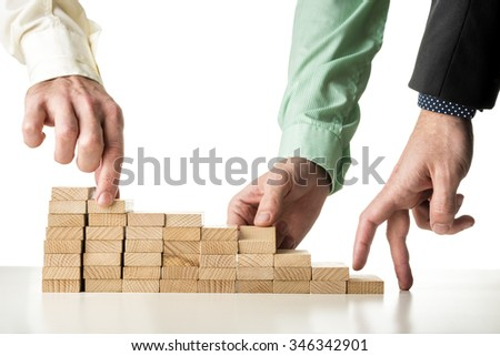 Teamwork and cooperation - two male hands assembling strong foundation of wooden pegs for the third hand to walk its fingers up the steps toward success. - stock photo