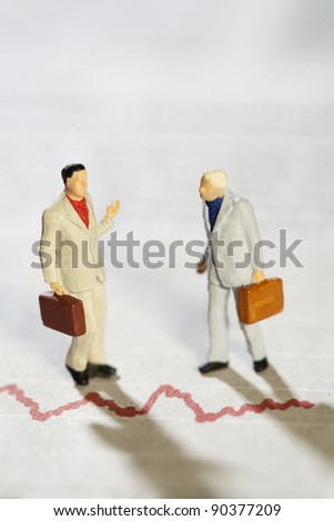 Teamwork And Discussion, two miniature model businessmen having a deep discussion above a red line graph. - stock photo