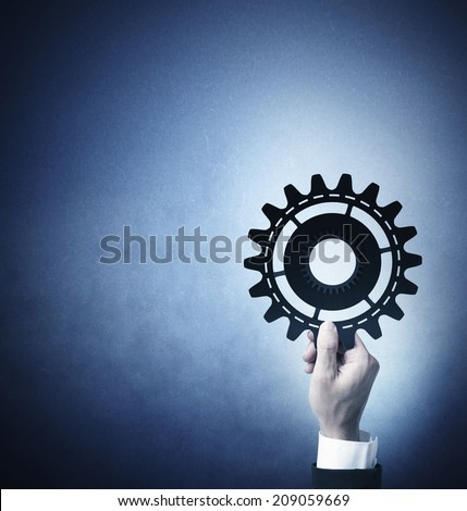 Teamwork and integration concept with businessman that holds a gear - stock photo