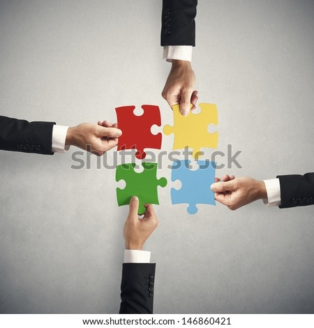Teamwork and partnership concept with puzzle - stock photo