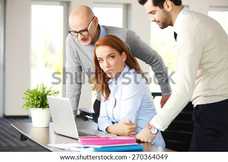 Teamwork at office. Executive businesswoman sitting at desk in front of computer while businessmen standing behind her.  Sales team working on business plan. - stock photo