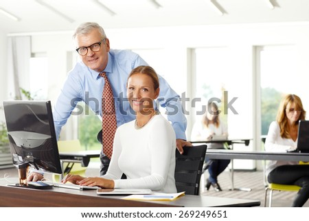 Teamwork at office. Portrait of senior financial manager giving advise to businesswoman while sitting in front of computer and analyzing financial data.  At background sitting business persons.  - stock photo