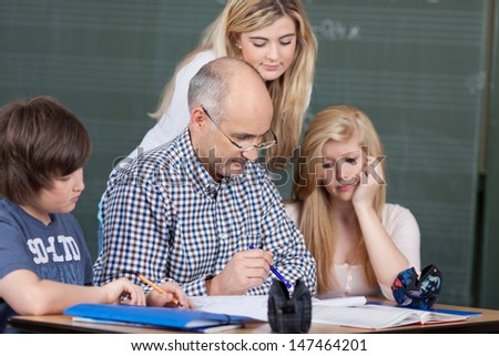Teamwork at school with a balding middle-aged male teacher and his young students grouped around some notes on a desk - stock photo