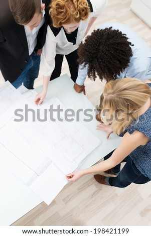 Teamwork at the office with a young business team bending over paperwork and statistics laid out on a table having a brainstorming session, high angle view - stock photo