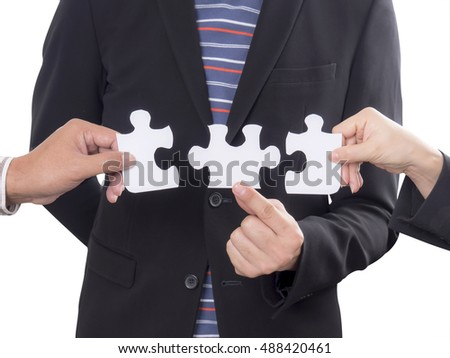 Teamwork business people assembling jigsaw puzzle on isolated / white background.