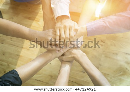 Teamwork concept,Business team standing hands together in the office. people joining hands holding altogether,jointly, simultaneously, abreast, cooperation success business concept,vintage color - stock photo