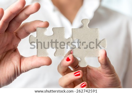 Teamwork concept using two puzzle pieces being fitted together by male and female hand in a challenge, brainstorming and solution concept. - stock photo