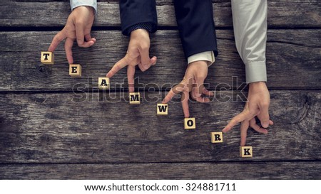 Teamwork concept with the word spelt out on wooden blocks in the form of a staircase with businessmen walking their fingers up the steps of success. - stock photo