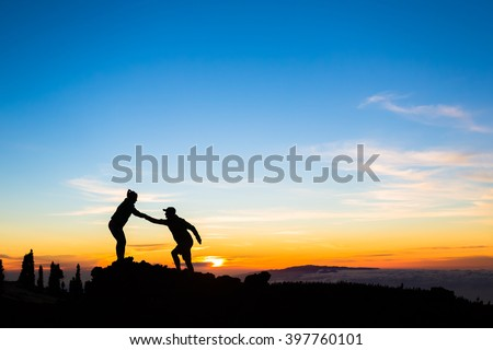 Teamwork couple helping hand trust help silhouette in mountains, sunset.Team of climbers man and woman hikers help each other on top of mountain beautiful inspirational sunset landscape Canary Islands - stock photo