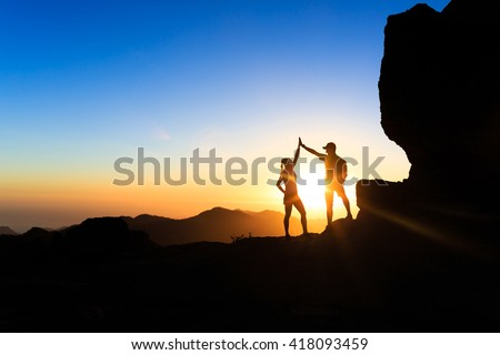 Teamwork couple helping hand trust help, silhouette success in mountains. Team of climbers man and woman. Hikers celebrate with hands up, help each other on top of mountain, happy climbing together. - stock photo